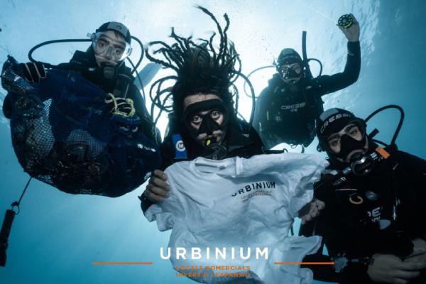 Buceadores sosteniendo la camiseta de Urbinium bajo en mar en la acción de limpieza del fondo marino llevada a cabo